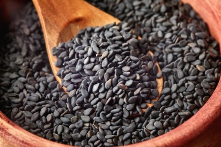 Close up of black sesame seeds in wooden spoon