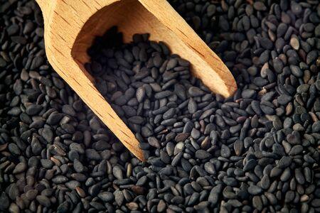 Close up of black sesame seeds in wooden scoop