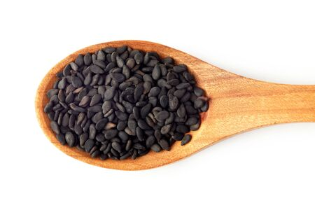 Black sesame seeds in wooden spoon isolated on white background