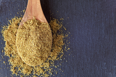 Ground cumin powder in wooden spoon. Top view with copy space