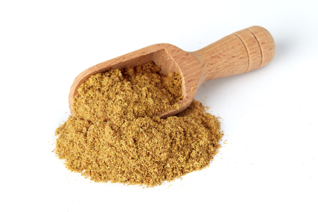 Ground cumin powder in wooden scoop isolated on white background Stockfoto