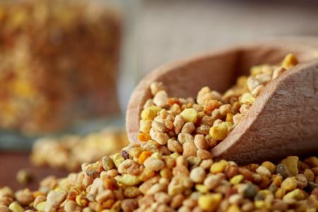 Close up of bee pollen grains in wooden scoop 版權商用圖片