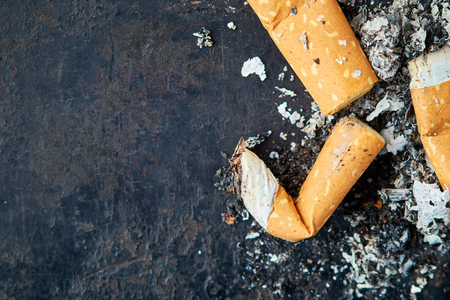 Cigarette butts on black rustic background. Top view with copy space
