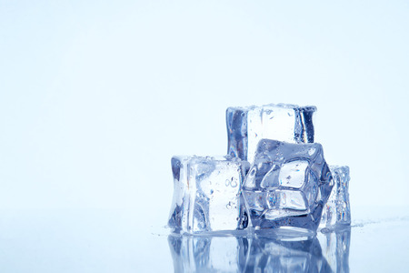 Wet square ice cubes on reflective light blue background. Copy space