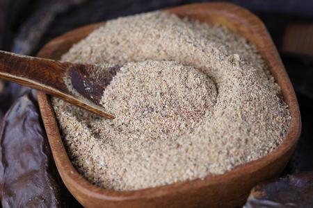 Ground carob (Ceratonia siliqua) powder in wooden bowl