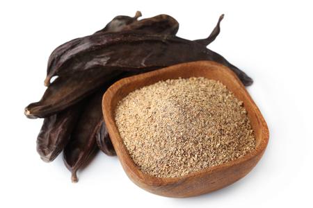Ground carob (Ceratonia siliqua) powder with carob bean pods isolated on white background