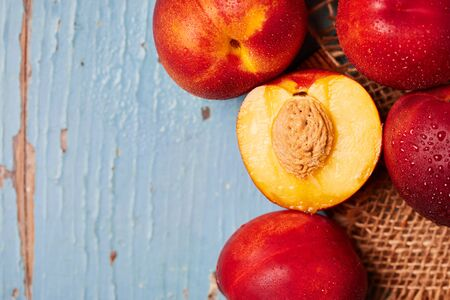 Fresh ripe nectarines on blue rustic wooden background. Top view with copy space