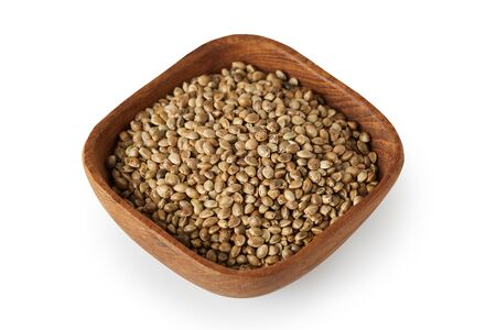 Organic whole hemp seeds in wooden bowl isolated on white background