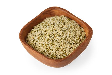 Organic shelled hemp seeds in wooden bowl  isolated on white background 免版税图像