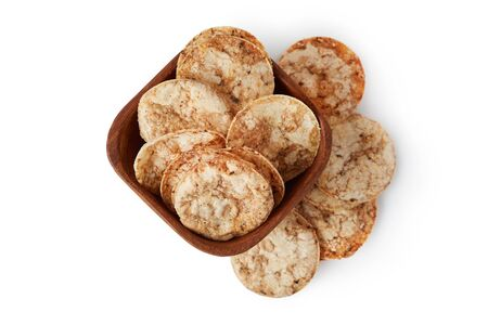 Brown rice chips isolated on white background. Healthy crispy snack
