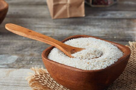 Psyllium (ispaghula) husk in wooden bowl on rustic background