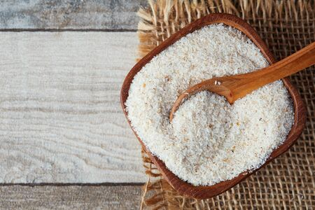 Psyllium (ispaghula) husk in wooden bowl on rustic background. Top view with copy space