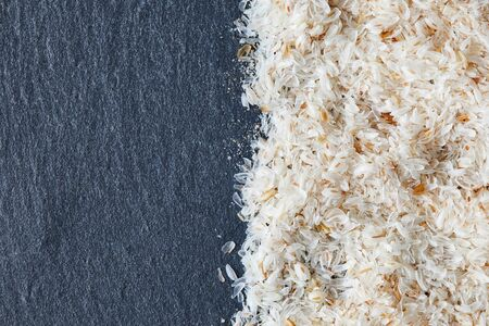 Psyllium (ispaghula) husk on black rustic background. Top view with copy space 免版税图像
