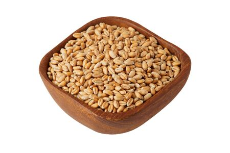 Raw wheat grain in wooden bowl isolated on white background