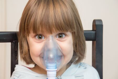 Beautiful girl using the inhalation mask Stock Photo
