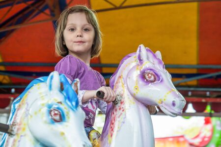 Young girl riding carousel horses Stock Photo