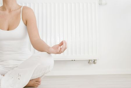 Young girl is sitting by a white heater Stock Photo - 7184505