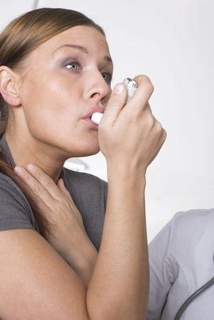 aparato respiratorio: Mujer con asma usando el inhalador  Foto de archivo
