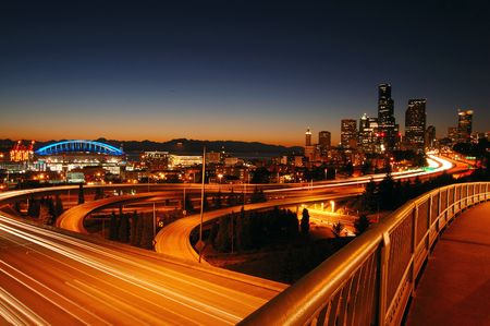 A night shot of freeways and Seattle downtown at the background