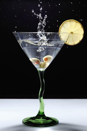 olive splashing into martini glass stock photo