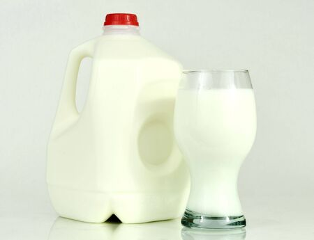 one gallon milk container and a glass of milk