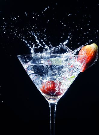 strawberry splashing into a glass of martini cocktail isolated in black Stock Photo
