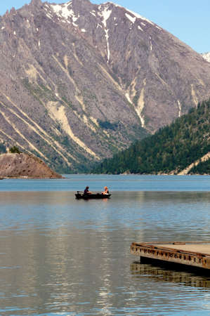 fishing boat underneath the mountains in the clear waters of coldwater lake