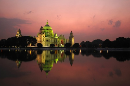 across: Majestic Victoria Memorial building reflected across lake at sunset