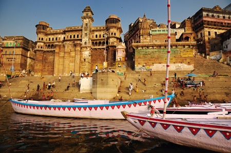 ghat: City of Varanasi with colorful boats and ancient historic palaces and buildings.