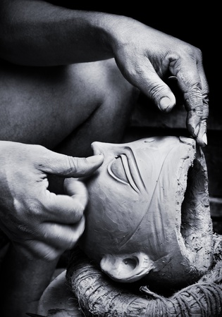 sculptor: Beautiful monocrome image of a potter creating a clay head of a goddess idol for Durga Puja festival in Kumartuli in Kolkata, India. Slight motion blur showing hand movement of the artist. Editorial