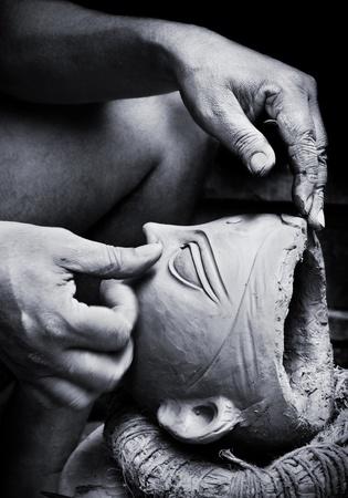alfarero: Monocrome hermosa imagen de un alfarero creando una cabeza de arcilla de un �dolo de la diosa Durga Puja Festival en Kumartuli en Calcuta, India. Desenfoque de movimiento leve movimiento de la mano de muestra de la artista.
