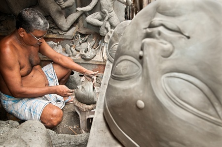 goddesses: CALCUTTA - AUGUST 15, 2011: An artisan creates heads of clay idols of goddesses on August 15, 2011 in Kumartuli, Calcutta, India. The idols are made for the Hindu festival of Dasara. Editorial