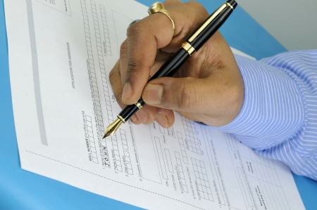 a gentleman filling up an application form for admission with a fountain pen photo