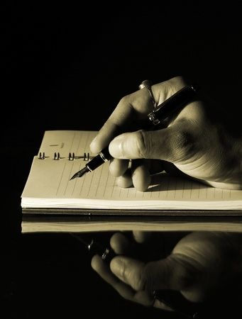 vintage vertical photo of a hand of a man writing in a diary with a fountain pen
