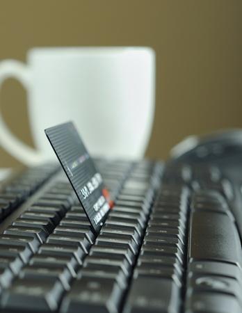 transaction: Internet winkelen via credit card, koffiekopje en muis op de achtergrond
