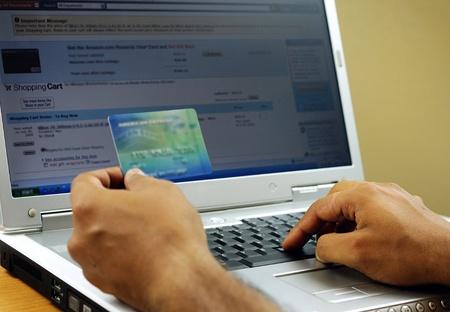 entering information: Internet shopper entering credit card information using laptop keyboard