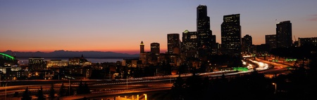 seattle skyline: Panoramic image of Seattle downtown buildings and adjoining freeways with sunset glow over the horizon Stock Photo