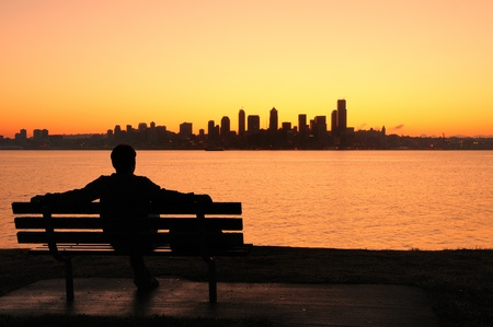 silhouette of a man sitting on a park bench watching the sun rise behind Seattle skyline