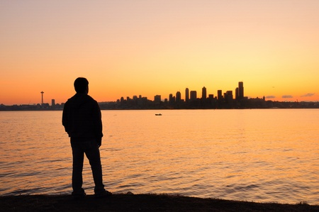 A young man watching the sun rise behing the Seattle skyline across the bay Stock Photo - 10466819