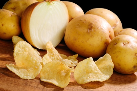 gease: Onion flavored extra crispy potato chips with potatoes and onions in the background over black