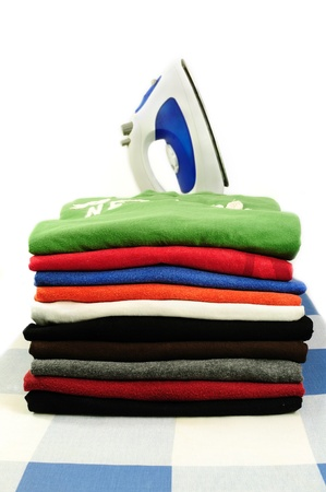 Colorful clothes pressed and folded with electric iron photo