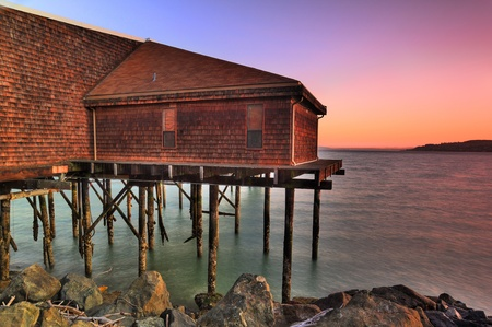 fishing cabin: Beautiful old tavern over waterfront at sunrise HDR image