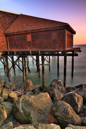 fishing huts: Beautiful old tavern over waterfront at sunrise HDR vertical image