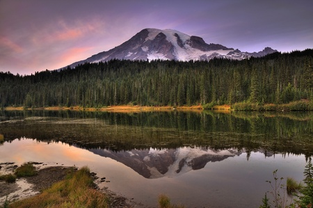 Mount Rainier reflected across the reflection lakes at dusk under a dramatic sky photo
