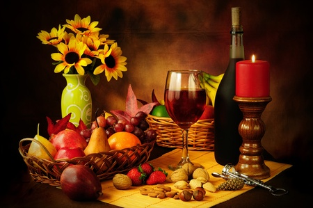 life styles: Beautiful still life image of red wine, fruits and nuts with dramatic lighting
