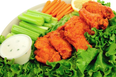 Delicious buffalo chicken wings served with celery, carrots and chunky blue cheese dip photo