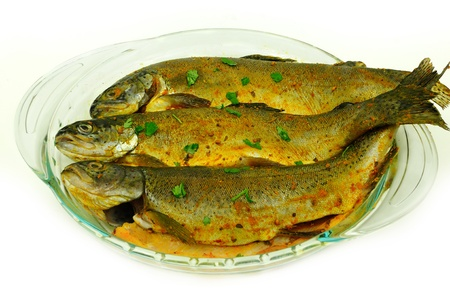 Fresh Trout fishes marinated in a glass bowl before cooking