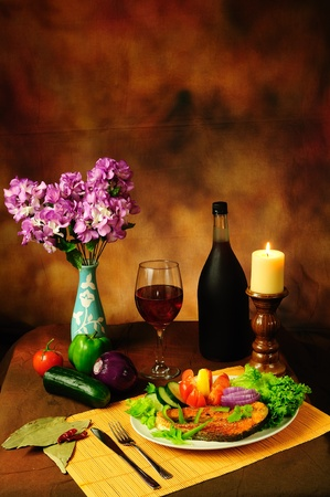 Still life of delicious dish of fish with salad and served with vintage red wine vertical image