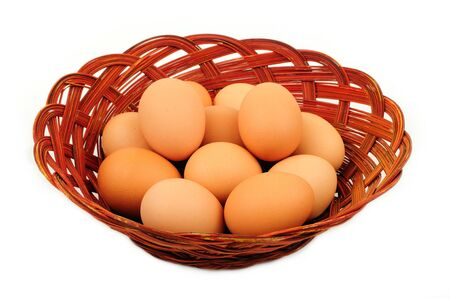 Fresh farm eggs in a basket isolated over white Stock Photo