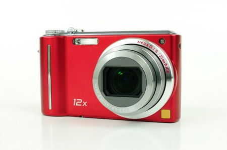 photo camera: Modern red compact high zoom digital camera over white